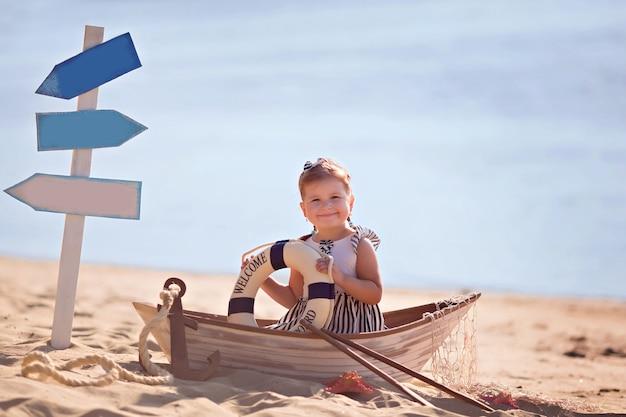 Dziewczynka siedzi w łodzi, ubrana jak marynarz na piaszczystej plaży