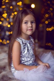 Dziewczynka siedzi w studio w sukience z choinką w boże narodzenie z długimi włosami