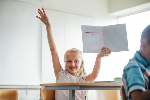 Dziewczynka siedzi w tabeli szkolnej z notebooka