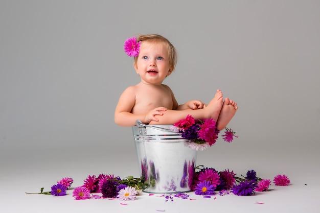 Dziewczynka siedzi w wiadrze kwiatów