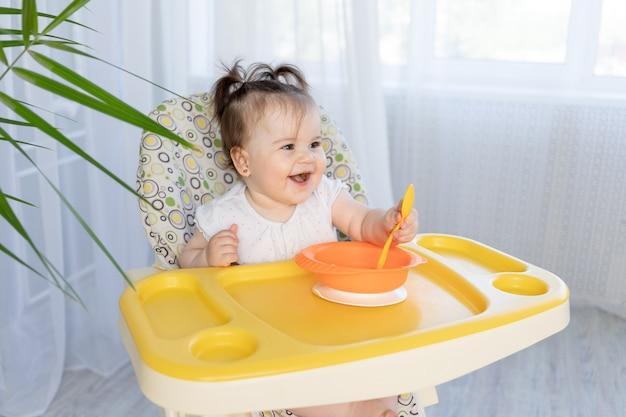 Dziewczynka siedzi w wysokim krzesełku i śmieje się, koncepcja jedzenia dla dzieci