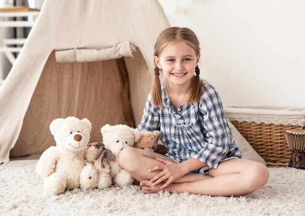 Dziewczynka siedzi ze skrzyżowanymi nogami w pobliżu misiów na podłodze pokoju z wigwamem