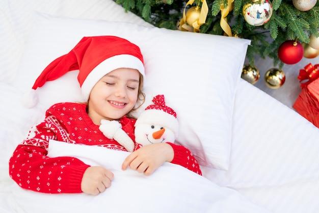 Dziewczynka śpi pod choinką w czerwonym swetrze i czapce świętego mikołaja w oczekiwaniu na nowy rok lub boże narodzenie w białym łóżku z bałwanem w ramionach