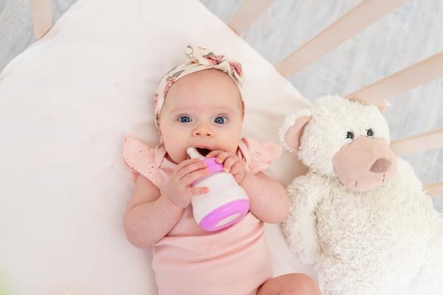 Dziewczynka ssie butelkę mleka w łóżeczku leżąc na plecach z zabawką w przedszkolu, koncepcja jedzenia dla dzieci