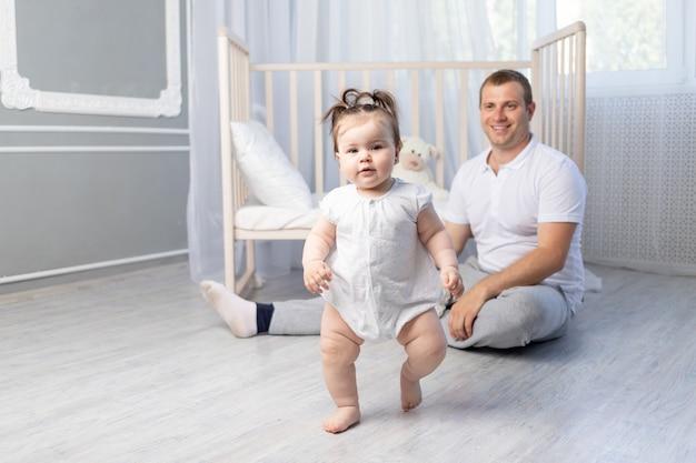 Dziewczynka stawia pierwsze kroki, tata uczy chodzić w przedszkolu, szczęśliwe ojcostwo