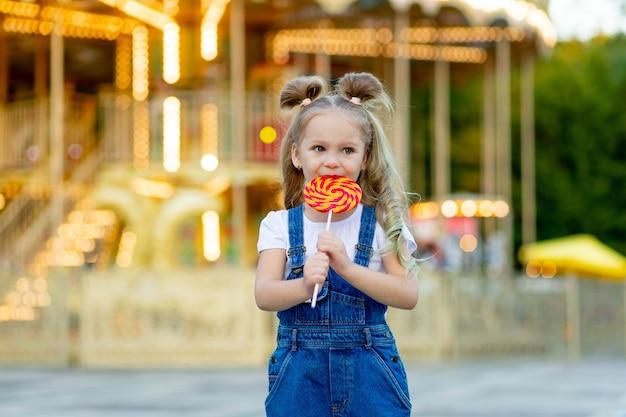 Dziewczynka stoi w parku rozrywki z dużym lollipopem