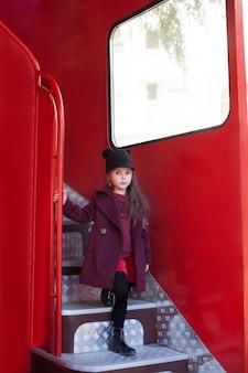 Dziewczynka stoi w pobliżu czerwonego angielskiego autobusu w płaszczu i kapeluszu. podróż dzieci dziecko w szkolnym autobusie. londyn czerwony autobus. wiosna. edukacja przedszkolna. dziecko nie chce chodzić do szkoły. uczennica