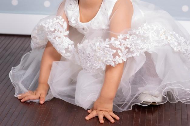 Dziewczynka sukienka chrzciny białej ścianie