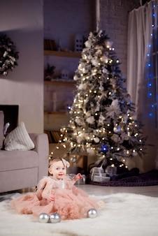 Dziewczynka świętuje nowy rok w pobliżu choinki w domu.