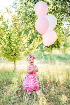 Dziewczynka świętuje swój pierwszy dzień urodzinowy z tortem dla smakoszy i balonami. dzień dziecka