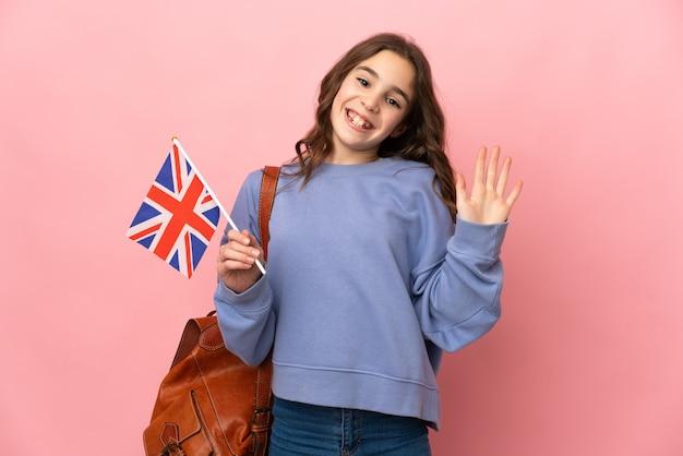 Dziewczynka trzyma flagę zjednoczonego królestwa na białym tle na różowym tle, salutując ręką z happy wypowiedzi
