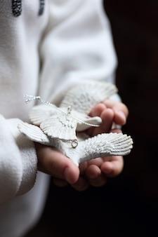 Dziewczynka trzyma gołębie żółw w dłoniach. każda gołębica żółwia jest misternie wyrzeźbiona przez rzemieślnika z żywicy, aby wyglądała realistycznie jak prawdziwe gołębie.