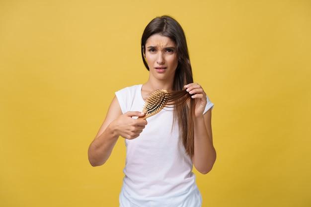 Dziewczynka trzyma grzebień, z którego wypadły jej włosy. pojęcie zdrowia włosów.