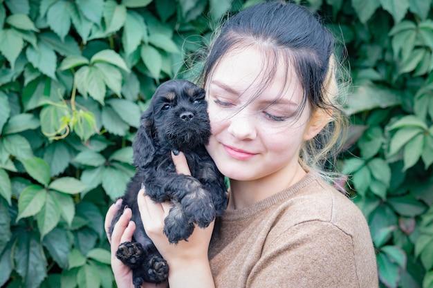 Dziewczynka trzyma małego czarnego szczeniaka cocker spaniela, przyciskając go do policzka, jej oczy są zamknięte ze szczęścia.