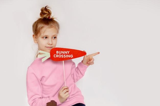 """Dziewczynka trzyma marchewkę z napisem """"króliczek"""""""