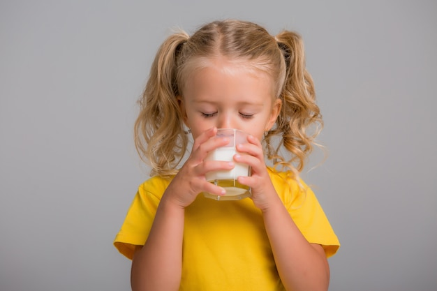 Dziewczynka trzyma szklankę mleka na jasnym tle, miejsca na tekst