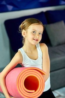 Dziewczynka trzyma w dłoni fitness joga różowy mat
