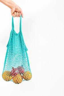 Dziewczynka trzyma w dłoni owoce w siatkowej torbie wielokrotnego użytku, biała ściana z miejscem na kopię. koncepcja zero waste, świadoma konsumpcja.