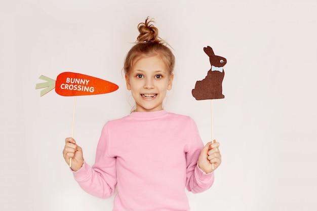 Dziewczynka trzyma w dłoniach marchewkę i brązowego filcowego królika i uśmiecha się