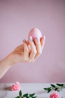Dziewczynka trzyma w ręku różowe jajko wielkanocne, różowe i marmurowe tło, minimalizm, kwiaty