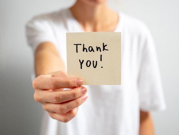 Dziewczynka trzyma w wyciągniętej dłoni papierową naklejkę z napisem - dziękuję.