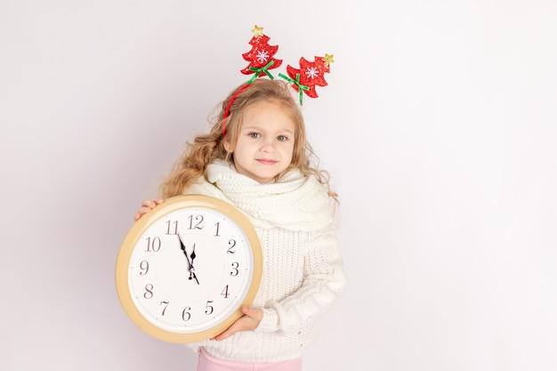 Dziewczynka trzyma zegar na białym tle na białym tle ze swetrem, miejsce na tekst, koncepcja nowego roku i świąt