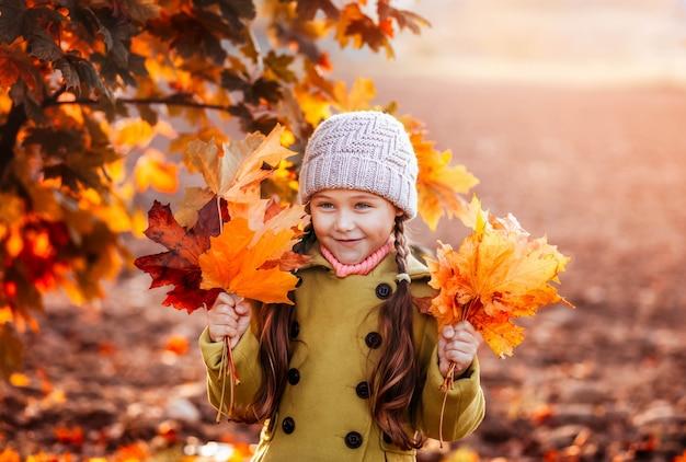 Dziewczynka trzymając w rękach pomarańczowe jesienne liście klonu