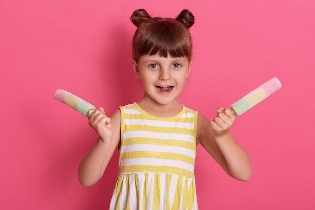 Dziewczynka trzymająca kolorowe lody na patyku, z podekscytowanym wyrazem twarzy, pozująca z radością, ubrana w biało-żółtą letnią sukienkę w paski na różowej ścianie.