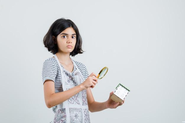 Dziewczynka trzymająca lupę nad modelem domu w koszulce, fartuchu i wyglądająca na zdziwioną,