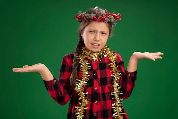 Dziewczynka ubrana w świąteczny wieniec w kraciastej sukience ze świecidełkiem wokół szyi zdezorientowana, rozkładając ręce na boki