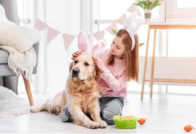 Dziewczynka ubrana w uszy królika do golden retriever psa na wielkanoc w słonecznym pokoju