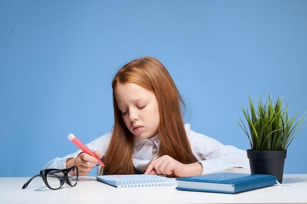 Dziewczynka uczennica dziecko robi pracę domową siedzi przy stole
