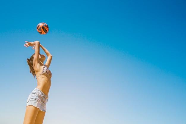 Dziewczynka uderzając w siatkówkę na plaży