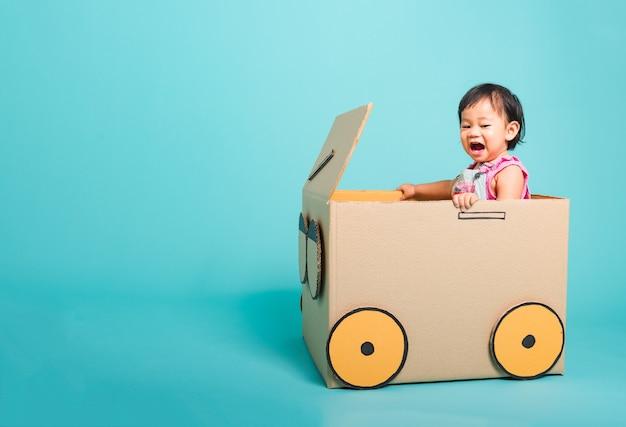 Dziewczynka uśmiech w prowadzeniu samochodu kartonowego