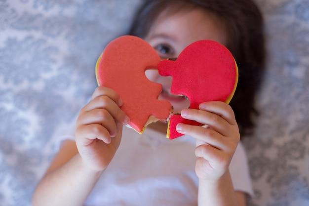 Dziewczynka uśmiecha się i trzyma serce w kształcie ciasteczka puzzle