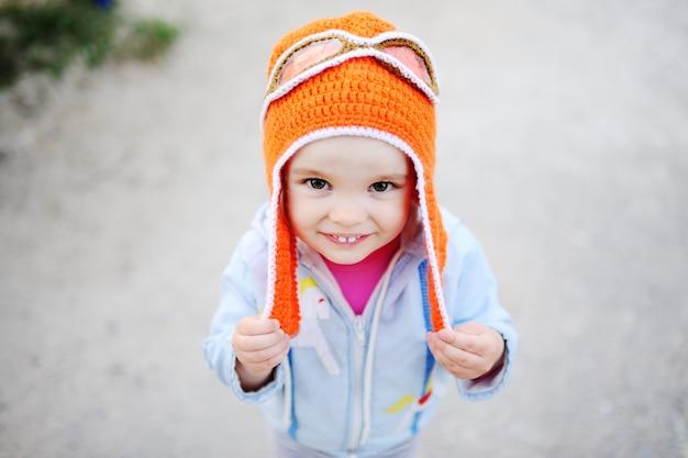 Dziewczynka uśmiecha się w aparacie w pilotowym kapeluszu