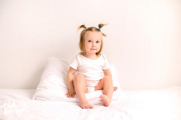 Dziewczynka uśmiecha się w białe szaty leżąc na łóżku z białą pościelą