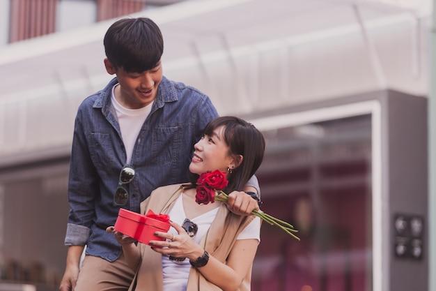 Dziewczynka uśmiecha się z pudełkiem czekoladek i róż