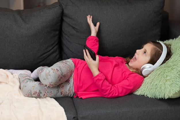 Dziewczynka w bezprzewodowych słuchawkach chłodzących, śmiejąc się na kanapie, słuchając ulubionej muzyki trzymając telefon za pomocą aplikacji mobilnej odtwarzacza online. ciesz się spokojnym nastrojem nosząc słuchawki w domu