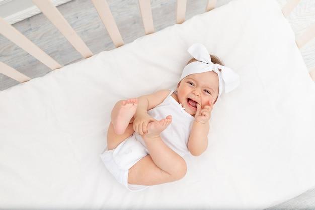 Dziewczynka w białych ubraniach leżącej w łóżeczku