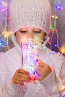 Dziewczynka w białym swetrze i czapce z dzianiny pije ze szklanych wielokolorowych lampek świątecznej girlandy. koncepcja kreatywnych świąteczny nastrój.