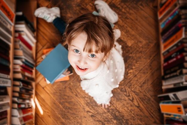 Dziewczynka w bibliotece z książkami w jej ręce. słodki maluch eksploruje półki z książkami