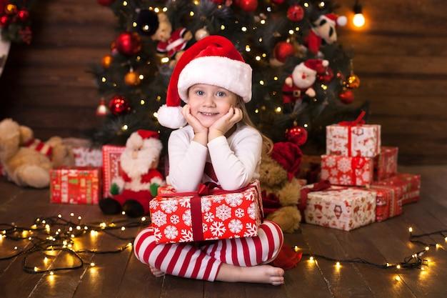 Dziewczynka w czapce mikołaja z prezentem na wigilię bożego narodzenia w salonie