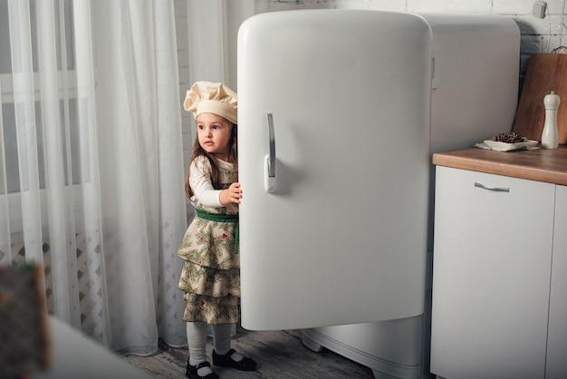 Dziewczynka w czapce szefa kuchni zagląda do lodówki