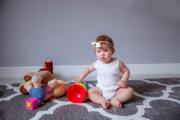Dziewczynka w domu siedzi na podłodze, bawiąc się zabawkami