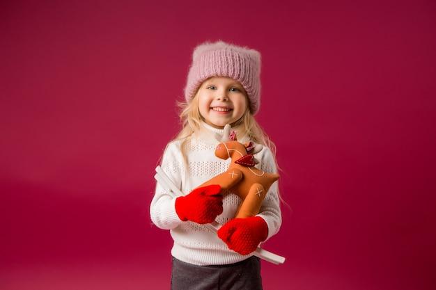 Dziewczynka w dzianinowym kapeluszu i rękawiczkach uśmiecha się i trzyma w dłoniach tekstylną zabawkę bożonarodzeniowego renifera