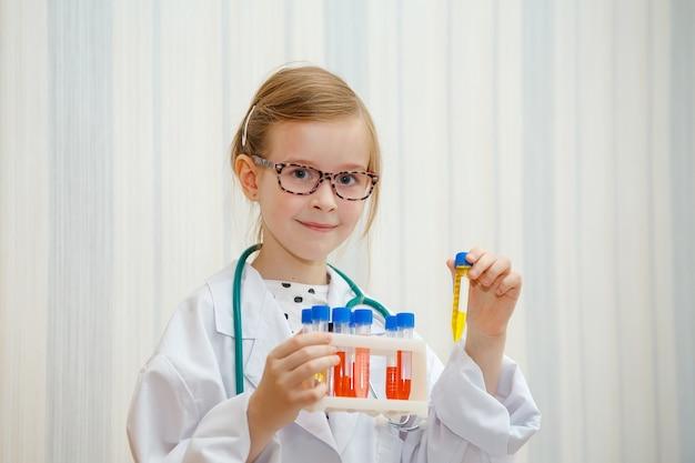 Dziewczynka w fartuchu lekarza bada probówki z testami. edukacyjna gra medyczna.