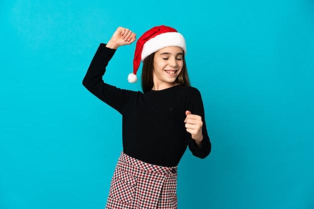 Dziewczynka w kapeluszu boże narodzenie na białym tle na niebieskim tle świętuje zwycięstwo