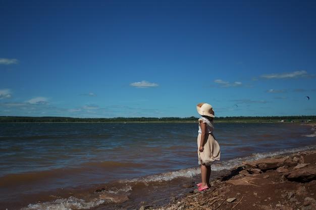 Dziewczynka w kapeluszu lato stojący nad morzem