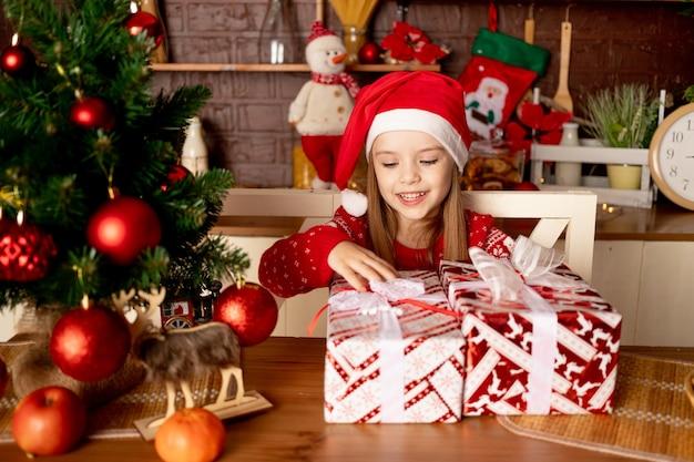 Dziewczynka w kapeluszu mikołaja z prezentami w ciemnej kuchni przy choince z czerwonymi kulkami raduje się i uśmiecha, koncepcja nowego roku i bożego narodzenia